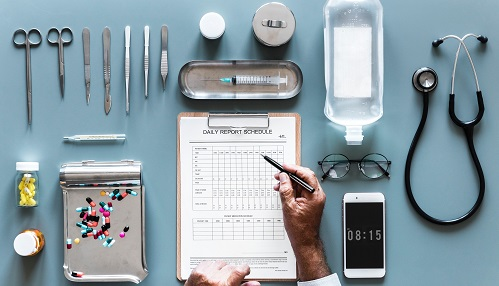 Photo of various medical paraphernalia arranged neatly on a desk surface around a clipboard, with a persons arm poised above it ready to take notes.